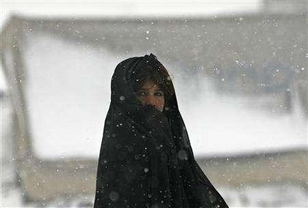 An Afghan girl stands outside her shelter at a refugee camp in Kabul February 14, 2008. The death toll from Afghanistan's harshest winter in recent living memory has hit 926, an official said on Saturday, adding the figure could rise further as access to remote areas improves with the thawing of snow. REUTERS/Omar Sobhani