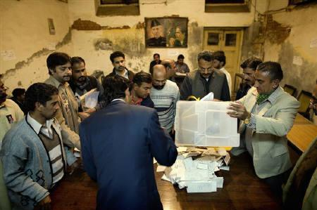 Election workers empty a ballot box at a polling station in Lahore February 18, 2008. Counting began on Monday after an election in Pakistan which was far less violent than feared, although it could result in a parliament set on driving U.S. ally President Pervez Musharraf from power.REUTERS/Jerry Lampen