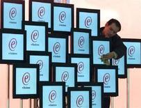<p>Un uomo sistema degli schermi a una fiera di elettronica. PEM/WS</p>