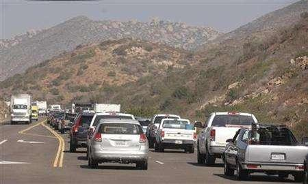 Traffic is backed up as residents return to town after being evacuated during wildfires in the Ramona area of San Diego County October 26, 2007. Staff of the Environmental Protection Agency warned the agency's head that he might have to resign if he blocked attempts by California to set first-ever limits on greenhouse gas emissions from cars, according to internal agency documents released by Congress on Tuesday. REUTERS/Phil McCarten