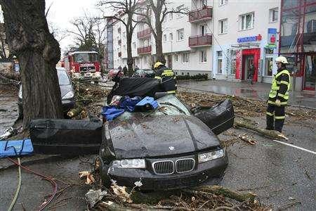 Firefighters stand near a car where one person was killed and three injured when a tree fell onto it during a storm nicknamed ''Emma'' in St. Poelten March 1, 2008. REUTERS/FF St. Poelten-Stadt/Handout