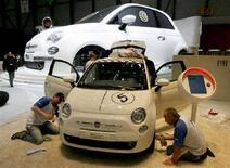 <p>Alcuni addetti allestiscono una Fiat 500 a Ginevra. REUTERS/Arnd Wiegmann (SWITZERLAND)</p>