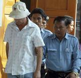 <p>Российский бизнесмен Александр Трофимов (слева) покидает зал суда в сопровождении полицейских, Пномпень, 14 марта 2008 года. Камбоджийский суд в пятницу приговорил крупного российского бизнесмена к 13 годам тюремного заключения за сексуальные домогательства к 14-летней девочке. (REUTERS/Stringer)</p>