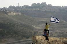 <p>Un attivista israeliano sventola la bandiera di Israele sulla cima di una collina vicino a Maale Adumim, insediamento ebraico in Cisgiordania. REUTERS/Gil Cohen Magen (WEST BANK)</p>