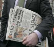 <p>Il portavoce dei genitori della piccola Madeleine McCann, Clarence Mitchell, fotografato oggi con una copia del Daily Express fuori dall'Alta Corte di Londra. REUTERS/Luke MacGregor (BRITAIN)</p>