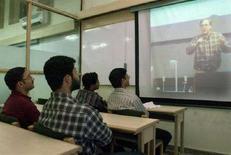 <p>Alcuni universitari asiatici assistono a una lezione in videoconferenza. REUTERS/Kamal Kishore</p>