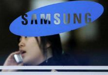 <p>Una donna al telefono dietro il logo di Samsung Group. REUTERS/Han Jae-Ho (SOUTH KOREA)</p>