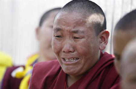 A protesting nun weeps after being beaten and detained by police near the Chinese Embassy visa section office in Kathmandu March 25, 2008. REUTERS/Gopal Chitrakar