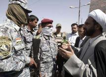 """<p>Представитель лидера иракских шиитов Моктады аль-Садра (справа) общается с сотрудниками одной из служб безопасности страны в Багдаде 29 марта 2008 года. Духовный лидер иракских шиитов Моктада аль-Садр призвал своих сторонников 9 апреля провести широкомасштабную демонстрацию против """"оккупации"""" страны войсками США. (REUTERS/Kareem Raheem)</p>"""