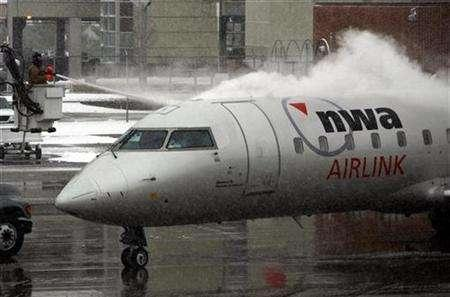 A Northwest Airlines plane is de-iced on the runway at Des Moines International Airport in Des Moines, Iowa, November 21, 2007. REUTERS/Shannon Stapleton