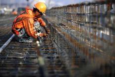<p>Due uomini lavorano con delle barre d'acciaio. REUTERS/John Javellana</p>