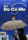 <p>Un uomo cammina davanti ad una vetrina con il logo NTT DoCoMo. REUTERS/Issei Kato (JAPAN)</p>
