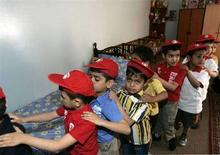 <p>Alcuni bambini in fila festeggiano l'Arab Orphan Day in un orfanatrofio di Baghdad il 6 aprile 2008. REUTERS/Mahmoud Raouf Mahmoud (IRAQ)</p>
