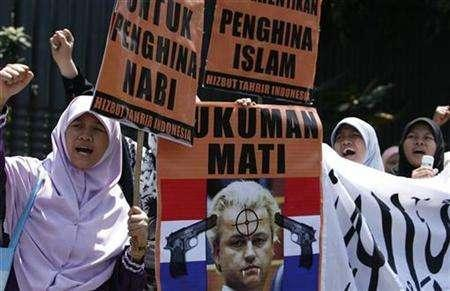 Muslim women shout slogans in front of a poster of Geert Wilders during a rally outside the Dutch Embassy in Jakarta April 1, 2008. REUTERS/Beawiharta