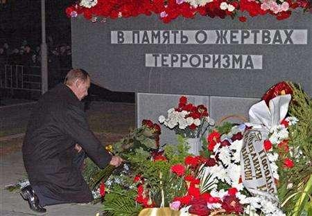 Vladimir Putin lays flowers at the memorial near the Dubrovka theatre in southeast Moscow, October 23, 2003. REUTERS/Pool/Sergei Ilnitsky