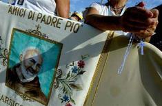 <p>Fedeli di Padre Pio recitano il rosario a San Giovanni Rotondo il 30 luglio 2004. REUTERS/Tony Gentile</p>
