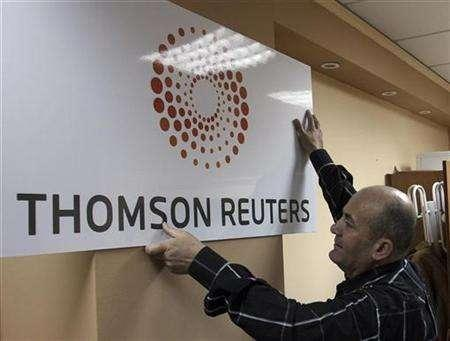 A man puts up the new Thomson Reuters signage at the office in Tirana April 17, 2008. REUTERS/Arben Celi