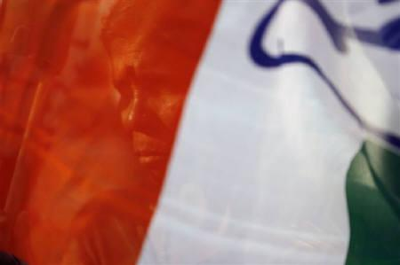 A supporter of India's ruling Congress party is seen through the party's flag at an election rally in Bangalore May 7, 2008. REUTERS/Arko Datta