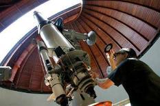 """<p>Отец Эммануэль Каррьера настраивает телескоп в обсерватории Ватикана в предместьях Рима, 23 июня 2005 года. Вера в Бога не противоречит возможности существования """"братьев-инопланетян"""", которые могут находиться на более высокой ступени развития чем люди, считает глава обсерватории Ватикана, 45-летний священник-иезуит Хосе Габриель Фунес. (REUTERS/Tony Gentile)</p>"""