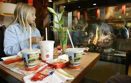 A young girl eats next to a fireplace at the newly designed interior of the McDonalds fast food restaurant in Wolfratshausen south of Munich in this June 27, 2007 file photo. REUTERS/Michaela Rehle