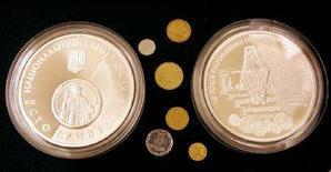 <p>Две монеты номиналом в 100 гривен на презентации в центральном банке Украины в Киеве 30 августа 2006 года. Премьер-министр Украины Юлия Тимошенко заявила, что поддерживает независимость Национального банка и считает его мнение приоритетным в вопросах курсообразования и монетарных вопросах. (REUTERS/Gleb Garanich)</p>
