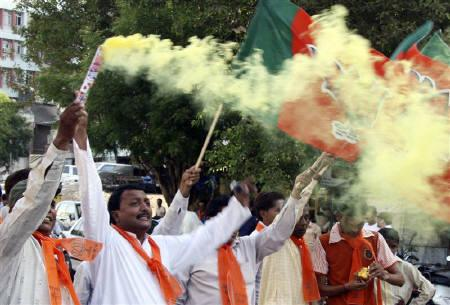 Party workers of Bharatiya Janata Party (BJP) light smoke flares to celebrate the party's victory in the state elections in Karnataka, outside the party's headquarters in Ahmedabad May 25, 2008. REUTERS/Amit Dave