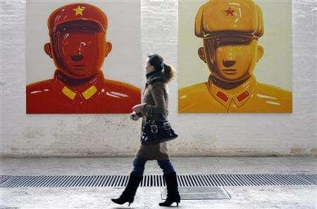 A visitor views paintings by Chinese artist Shen Jingdong titled ''Hero No. 12'' (L) and ''Hero No. 17'' (R) at an art gallery in Beijing in this December 4, 2006 file photo. REUTERS/Claro Cortes IV/Files