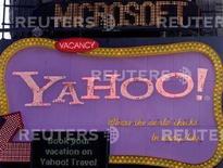 <p>Un cartellone pubblicitario di Yahoo. Sullo sfondo il nome di Microsoft passa su un tabellone di informazione elettronica. REUTERS/Joshua Lott</p>