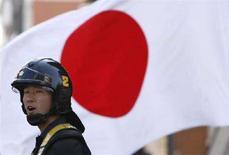 <p>Сотрудник полиции на фоне флага Японии у российского посольства в Токио 7 февраля 2008 года. Япония планирует снять некоторые санкции с Северной Кореи в ответ на обещание Пхеньяна провести повторное расследование относительно судьбы японских граждан, похищенных северокорейскими агентами несколько десятков лет назад. (REUTERS/Issei Kato)</p>