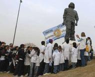 """<p>Alcuni alunni delle scuole riuniti attorno alla statua eretta per ricordare Ernesto """"Che"""" Guevara e realizzata da Andres Zerneri a Rosario, il luogo che ha visto nascere il rivoluzionario. REUTERS/Jose Granata</p>"""