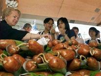 <p>Turisti giapponesi assaggiano delle salsicce esposte in una bancarella a Berna. REUTERS/Ruben Sprich</p>