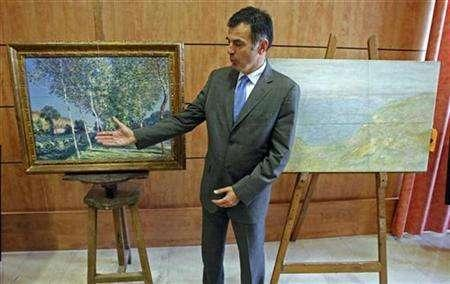 State prosecutor Jacques Dallest displays stolen paintings found after the arrest of 10 people in Marseille, France, June 5, 2008. REUTERS/Jean-Paul Pelissier