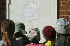 <p>Alcune persone leggo i risultati elettorali ad Harare REUTERS/Philimon Bulawayo</p>
