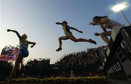 Jennifer Barringer (C) leaps over the water just behind Anna Willard (L) on her way to winning her semifinal heat in the women's 3000 meter steeplechase at the U.S. Olympic Track and Field Trials in Eugene, Oregon June 30, 2008. REUTERS/Mike Blake