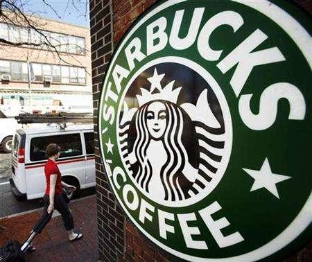 A woman walks past a Starbucks store in Somerville, Massachusetts April 24, 2008. REUTERS/Brian Snyder