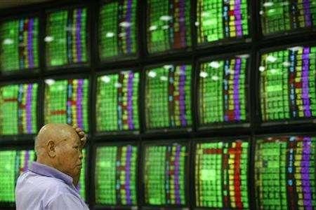 A man looks at stock market monitors in Taipei June 27, 2008. REUTERS/Nicky Loh