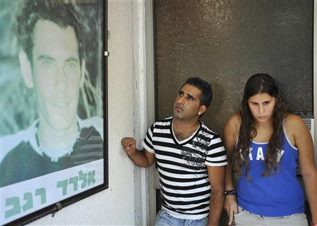 Israelis stand next to a picture depicting reserve soldier Eldad Regev outside his family's home in the northern city of Kiryat Motzkin July 16, 2008. REUTERS/Amir Cohen