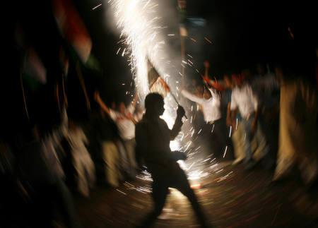 Supporters of the ruling Congress party celebrate outside party president Sonia Gandhi's residence in New Delhi July 22, 2008. Prime Minister Manmohan Singh's government won a vote of confidence in parliament on Tuesday, ensuring the survival of the ruling coalition and a civilian nuclear deal with the United States. REUTERS/Adnan Abidi