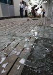<p>Жители убирают осколки стекол в центре города Хатинохе после землетрясения на севере Японии 24 июля 2008 года. Более 100 человек получили ранения в результате мощного землетрясения, которое произошло на севере Японии в среду вечером, вызвав перебои в работе нескольких крупных заводов. (REUTERS/Issei Kato)</p>