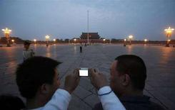 <p>Un ragazzo fotografa l'alzabandiera in piazza Tiananmen a Pechino. REUTERS/David Gray (CHINA)</p>