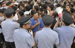<p>Poliziotti cercano di mantenere l'ordine davanti a una rivendita di biglietti per i Giochi olimpici del prossimo agosto. Pechino, 25 luglio 2008. REUTERS/Joe Chan (Cina)</p>