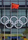 <p>Флаг Китая развевается перед олимпийскими кольцами, размещенными на здании крытого стадиона в Пекине, 22 июля 2008 года. Ирак не сможет принять участие в пекинской Олимпиаде, которая стартует 8 августа 2008 года, из-за того, что правительство страны распустило Национальный олимпийский комитет, сообщил Хуссейн аль-Амиди, генеральный секретарь НОК Ирака. (REUTERS/David Gray)</p>