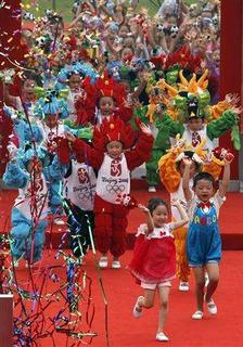 Children dressed in Olympic costumes run onto the stage during the official opening ceremony for the Olympic village in Beijing July 27, 2008. REUTERS/David Gray