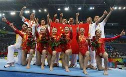 <p>Женская сборная Китая по спортивной гимнастике радуется победе в командных соревнованиях 13 августа 2008 года. Женская сборная КНР выиграла командные соревнования по спортивной гимнастике. (REUTERS/Mike Blake)</p>