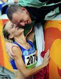 <p>Elisa Rigaudo festeggia con il suo partner la medaglia di bronzo nella marcia 20km alle Olimpiadi di Pechino. REUTERS/Dylan Martinez</p>