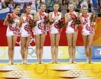 <p>Сборная России по художественной гимнастике празднует победу в групповых упражнениях в Пекине 24 августа 2008 года. Сборная России по художественной гимнастике завоевала золото в групповых упражнениях. REUTERS/Yves Herman</p>