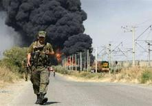 <p>Грузинский военнослужащий идет по дороге на фоне клубов дыма, поднимающихся от горящего состава с горючим недалеко от Гори 24 августа 2008 года. Железнодорожный состав, перевозивший горючее, взорвался недалеко от города Гори, сообщила полиция в воскресенье, добавив, что речь может идти о подрыве поезда на мине. (REUTERS/David Mdzinarishvili)</p>
