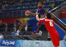 <p>Игрок сборной Франции Даниэль Нарцисс пытается переиграть Асгейра Орна Халлгримссона из сборной Исландии в Пекине 24 августа 2008 года. Мужская сборная Франции по гандболу выиграла золотые медали пекинской Олимпиады. REUTERS/Jacky Naegelen</p>