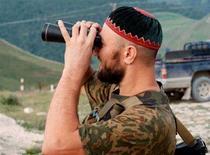 <p>Боевик-исламист наблюдает за передвижениями российских войск в Ботлихском районе Дагестана, 12 августа 1999 года. Тележурналист Абулла Алишаев, известный борьбой с радикальными формами ислама, был убит в Дагестане, сообщили в среду местные правоохранительные службы. REUTERS/Str Old</p>