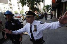 <p>Un poliziotto newyorkese allontana i passanti dal luogo di un incidente. La foto risale al 30 maggio scorso. REUTERS/Chip East</p>